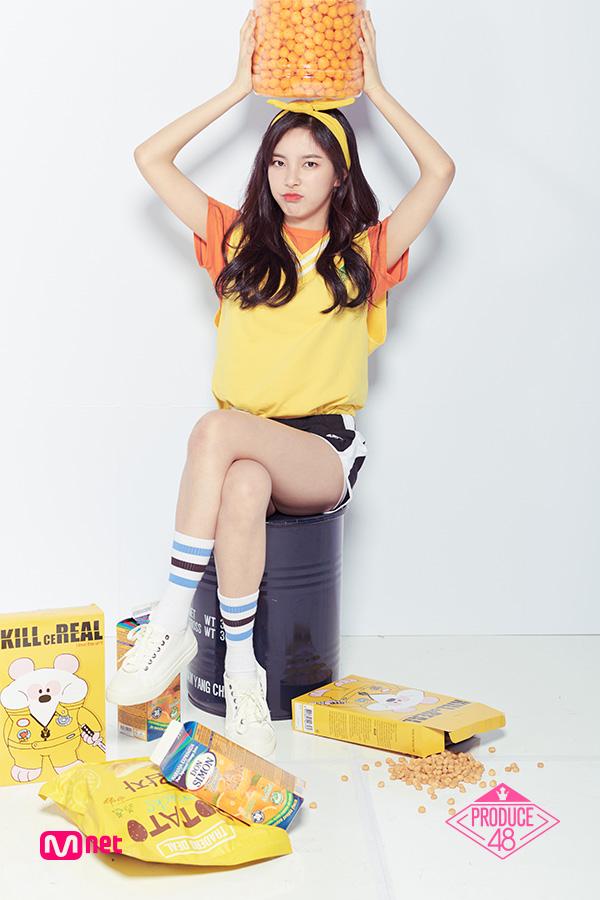 Tags: K-Pop, Television Show, Shin Suhyun, Orange Shirt, Hair Ornament, Wavy Hair, Black Shorts, White Background, Yellow Shirt, Shorts, Chin In Hand, Crossed Legs