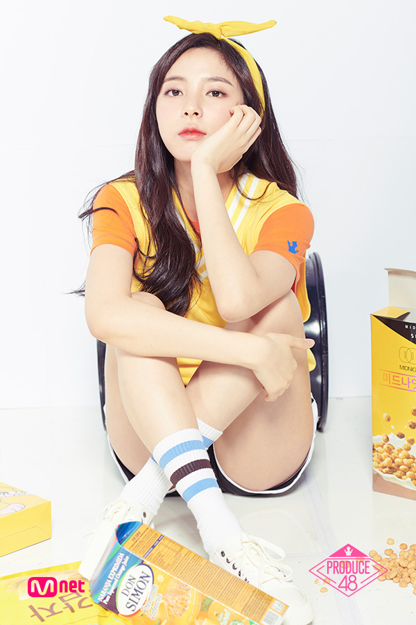 Tags: Television Show, K-Pop, Shin Suhyun, White Background, Orange Shirt, Sitting On Ground, Shorts, Chin In Hand, Crossed Legs, Shoes, Yellow Shirt, Bow