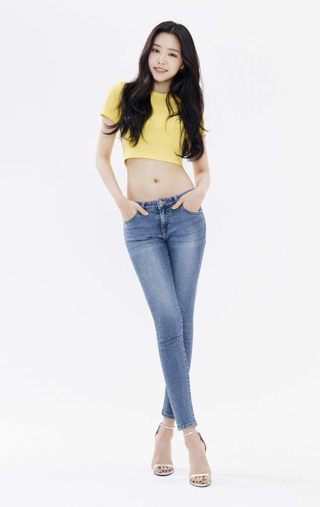 Tags: K-Pop, Apink, Son Na-eun, Hand In Pocket, Sandals, Crossed Legs (Standing), Grin, Blue Pants, Midriff, Jeans, Yellow Shirt, Light Background