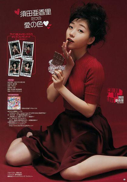 Tags: J-Pop, SKE48, AKB48, Suda Akari, Red Shirt, Brown Skirt, High Heels, Eating, Red Background, Sitting On Ground, Skirt, Finger To Lips