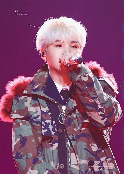 Tags: K-Pop, BTS, Suga, Singing, Fur, White Hair, Fur Trim, Purple Background, Coat, Stage, Black Eyes, Camouflage Print