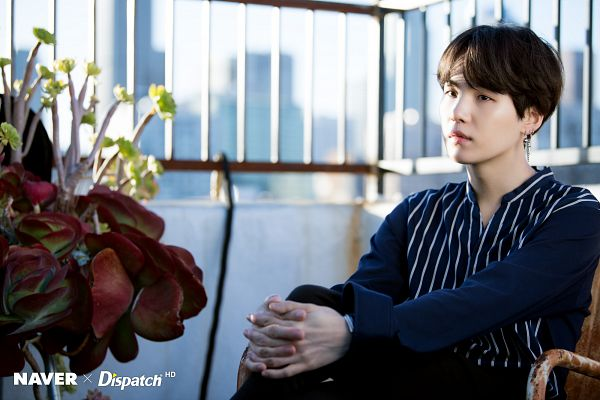 Tags: K-Pop, BTS, Suga, Bracelet, Looking Ahead, Outdoors, Chair, Striped Shirt, Hand On Leg, Black Pants, Plant, Sky