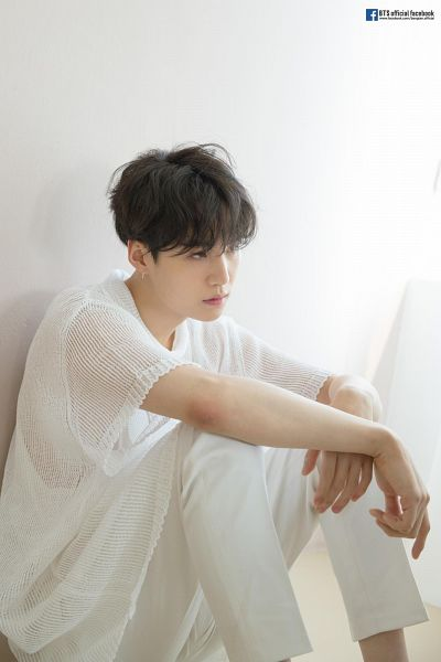 Tags: K-Pop, BTS, Suga, White Outfit, Sitting On Ground, White Pants, English Text, Text: Artist Name, Short Sleeves, Wall, Light Background, Shadow