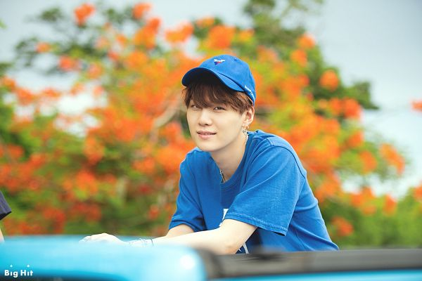 Tags: K-Pop, BTS, Suga, Hat, Short Sleeves, Outdoors, Close Up, Bracelet, Black Eyes, Text: Company Name, English Text, Blue Outfit