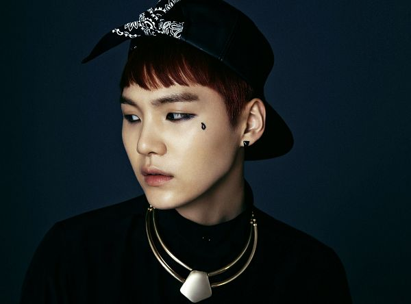 Tags: K-Pop, Bangtan Boys, Suga, Necklace, Black Headwear, Black Shirt, Red Hair, Tattoo, Blue Background, Hat, Baseball, Looking Away