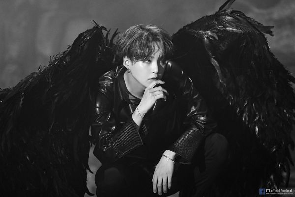 Tags: K-Pop, BTS, Suga, English Text, Angel Wings, Looking Up, Leather Shirt, Wavy Hair, Text: Artist Name, Monochrome, Crouching, Text: URL