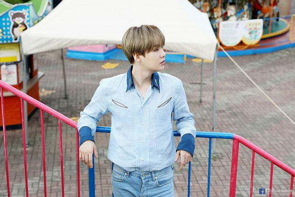 Tags: K-Pop, BTS, Suga, English Text, Text: URL, Outdoors, Looking Away, Text: Artist Name, Blue Shirt, Jeans, Striped, Carousel