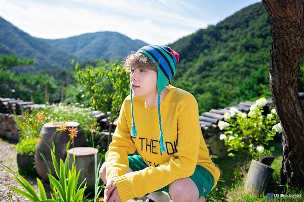 Tags: K-Pop, BTS, Suga, Hat, Text: URL, English Text, Green Shorts, Flower, Sky, Mound, Socks, Plant