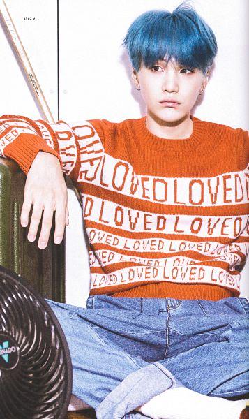 Tags: K-Pop, BTS, Suga, Blue Pants, Shoeless, Looking Away, Crossed Legs, Sitting On Ground, Socks, Sweater, Indoors, Fan
