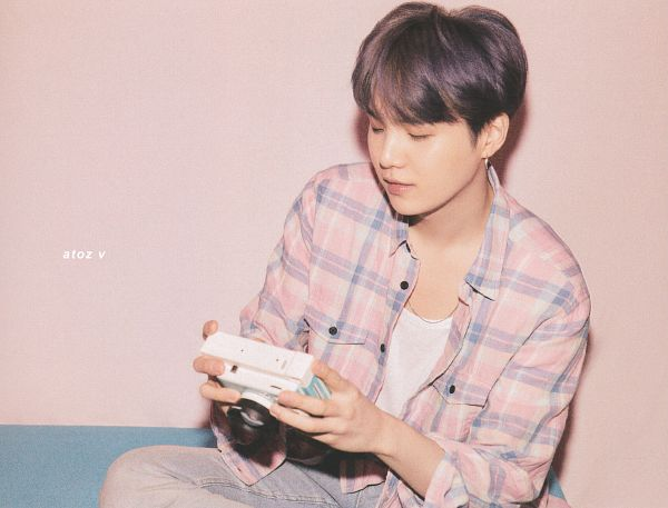 Tags: K-Pop, BTS, Suga, Pink Background, Plaided Shirt, Camera, Crossed Legs, Purple Hair, Wall, Necklace, Sitting On Couch, Plaided Print