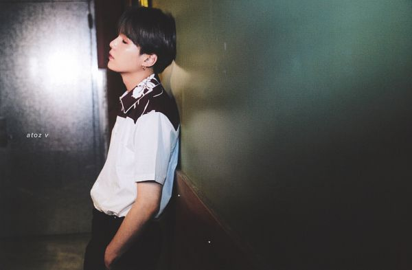 Tags: K-Pop, BTS, Suga, Eyes Closed, Serious, Black Pants, Indoors, Hand In Pocket, Wall, Short Sleeves, Leaning On Wall, Magazine Scan