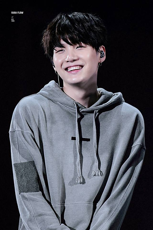Tags: K-Pop, BTS, Suga, Earbuds, Black Background, Hoodie, Stage, Black Eyes, Grin, Gray Shirt, Dark Background, Hood