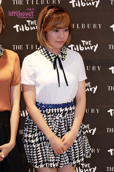 Tags: K-Pop, Girls' Generation, Sunny, Bare Legs, White Skirt, Medium Hair, Black Neckwear, Looking Down, Black Bow, Black Background, Clasped Hands, Skirt