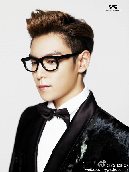 Tags: K-Pop, BIGBANG, T.O.P., Glasses, Black Neckwear, Black Jacket, Looking Away, Black Bow, Multi-colored Hair, Text: Company Name, Looking Down, Light Background