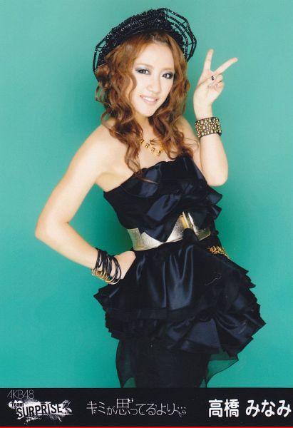 Tags: J-Pop, AKB48, Takahashi Minami, Green Background, Black Outfit, Black Headwear, V Gesture, Japanese Text, Black Dress, Text: Artist Name, Belt, Black Legwear