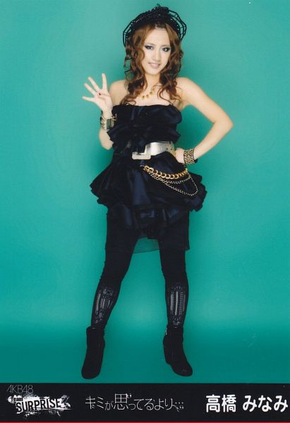 Tags: J-Pop, AKB48, Takahashi Minami, Black Outfit, Text: Artist Name, Hand On Hip, Japanese Text, Bracelet, Full Body, Bare Shoulders, Wavy Hair, Black Legwear