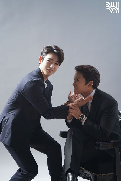 Tags: K-Drama, K-Pop, Got7, Park Jinyoung (Junior), Ji Sung, Two Males, Looking At Another, Flower Gesture, Duo, Sitting On Chair, Gray Background, Chair