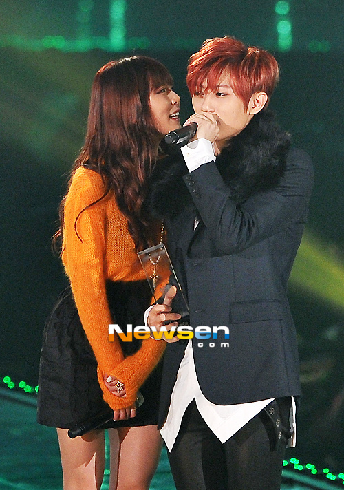 Tags: Cube Entertainment, K-Pop, Troublemaker, Hyuna, Jang Hyun-seung, Skirt, Green Background, Black Pants, Orange Shirt, Black Jacket, Black Outerwear, Duo