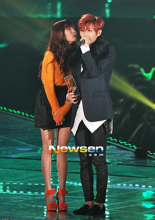 Tags: Cube Entertainment, K-Pop, Troublemaker, Jang Hyun-seung, Hyuna, Black Footwear, Black Skirt, High Heels, Green Background, Black Pants, Skirt, Orange Shirt