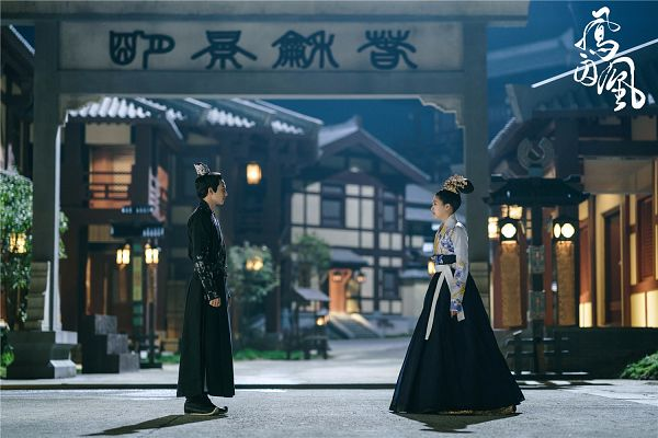 Tags: C-Drama, Guan Xiaotong, Song Weilong, Looking At Another, Night, Black Dress, Text: Series Name, Duo, Shoes, Hair Ornament, Traditional Clothes, Outdoors