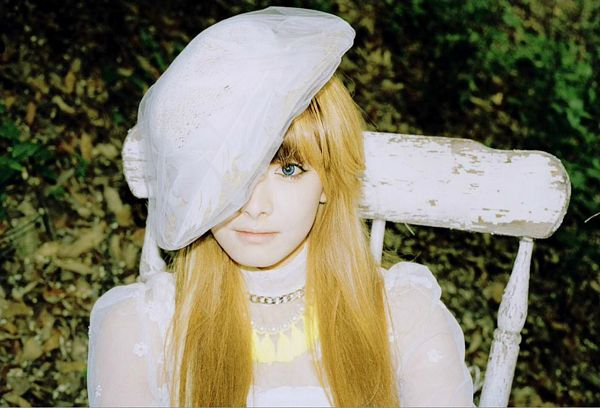 Tags: K-Pop, f(x), Victoria Song, Hat, Chair, Outdoors, White Headwear, Sitting On Chair, Blue Eyes, Necklace