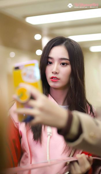 Tags: K-Pop, Xu Yiyang, Phone, Taking Selca, Pink Jacket, Looking at Phone, Smartphone, Pink Outerwear, Brown Background, XuYiyangBar