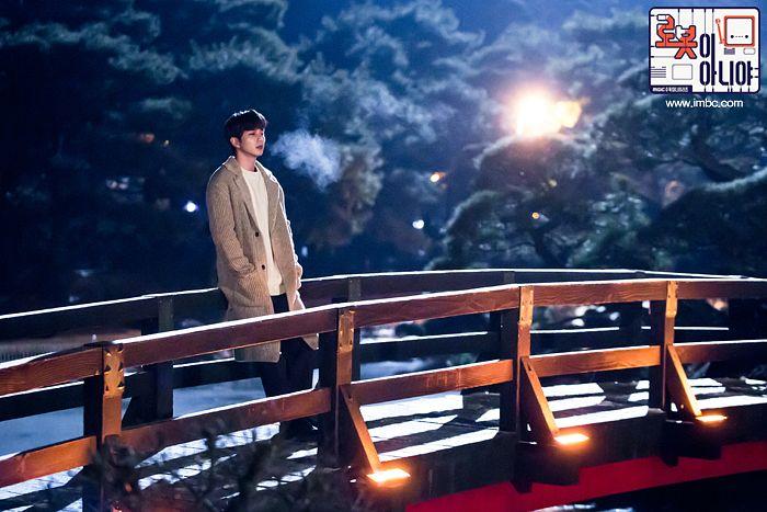 Tags: K-Drama, Yoo Seung-ho, Hand In Pocket, Plant, Brown Outerwear, Night, Bridge, Korean Text, Text: Series Name, Tree, Text: URL, Serious