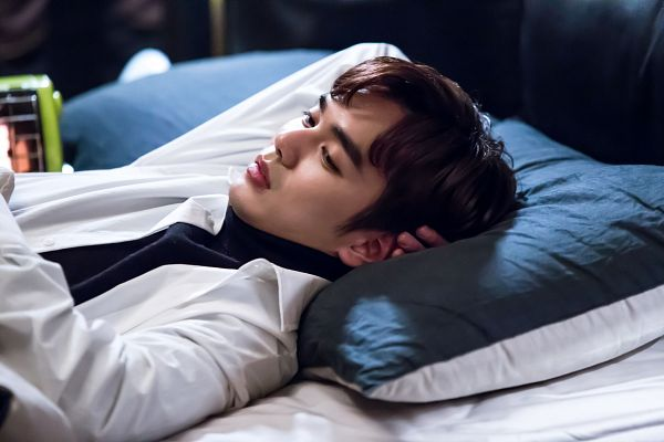 Tags: K-Drama, Yoo Seung-ho, Collar (Clothes), Turtleneck, Bed, Blanket, Black Shirt, Pillow, Serious, Laying Down, I'm Not a Robot
