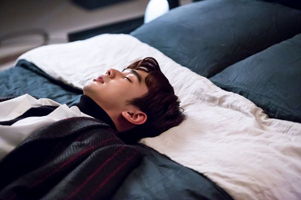 Tags: K-Drama, Yoo Seung-ho, Serious, Laying Down, Collar (Clothes), Eyes Closed, Turtleneck, Bed, Blanket, Black Shirt, Pillow, I'm Not a Robot