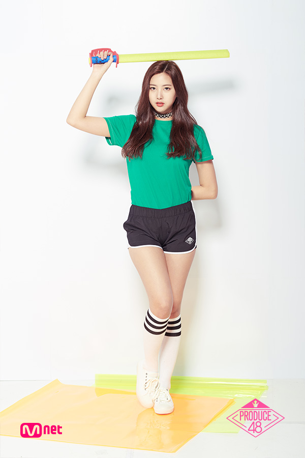 Tags: Television Show, K-Pop, Yoon Haesol, Text: Series Name, Shorts, Black Shorts, Holding Object, Arms Behind Back, Thigh Highs, Green Shirt, Light Background, Short Sleeves